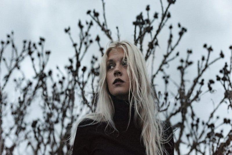 woman wearing black turtleneck sweater standing near tree