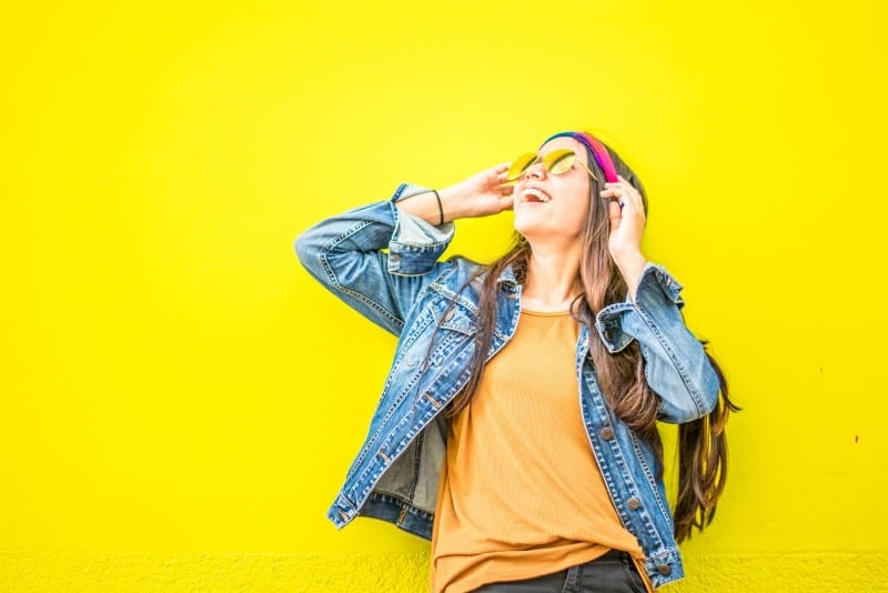 woman with sunglasses standing near yellow wall