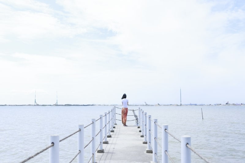 woman in white shirt standing on dock looking at water