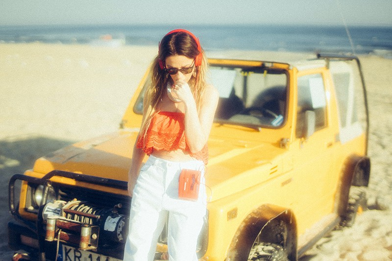 woman standing near yellow vehicle while listening music on a portable media player
