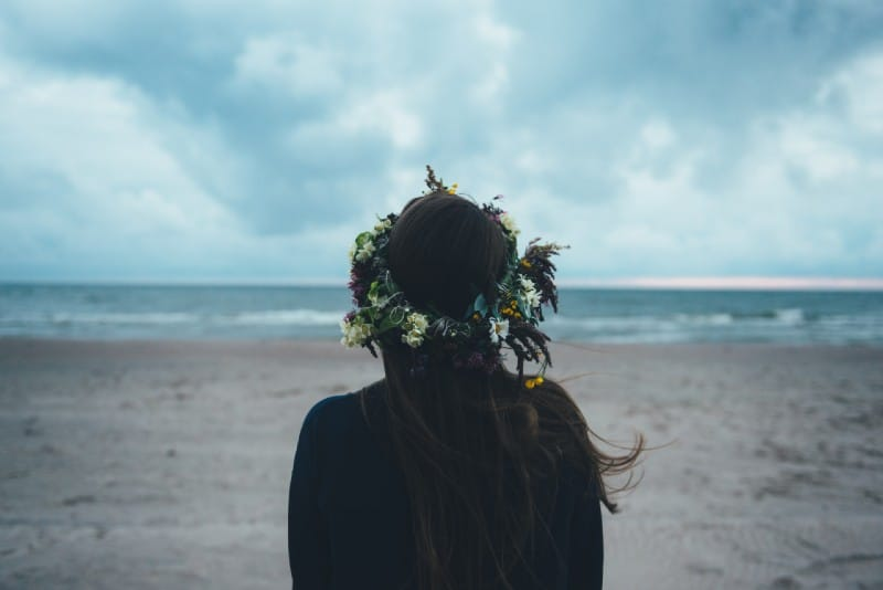 woman wearing flower crowns standing on beach looking at ocean