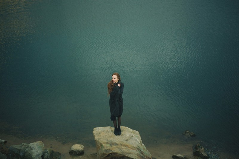 woman standing on the rock near the water