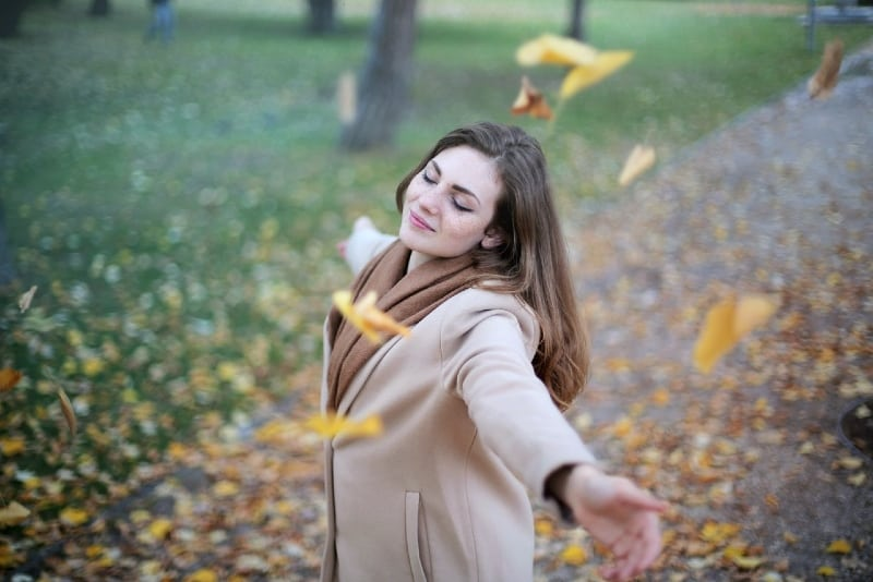 woman in coat eyes closed standing outdoor
