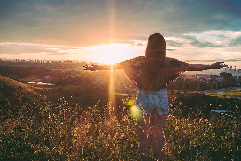 woman stands on mountain over field during sunset