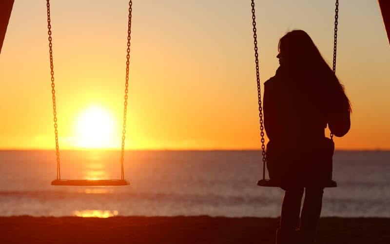 Sad woman alone swinging on the beach and looking the other seat