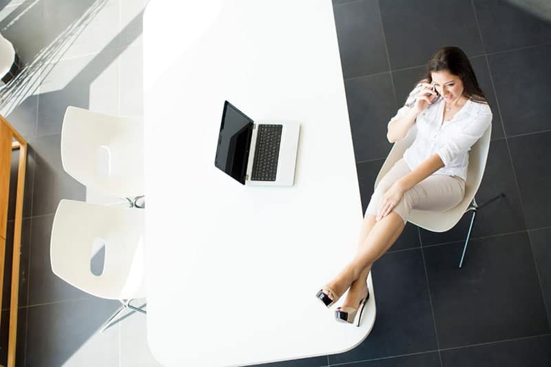 woman taking a phonecall with feet on the office table near a laptop