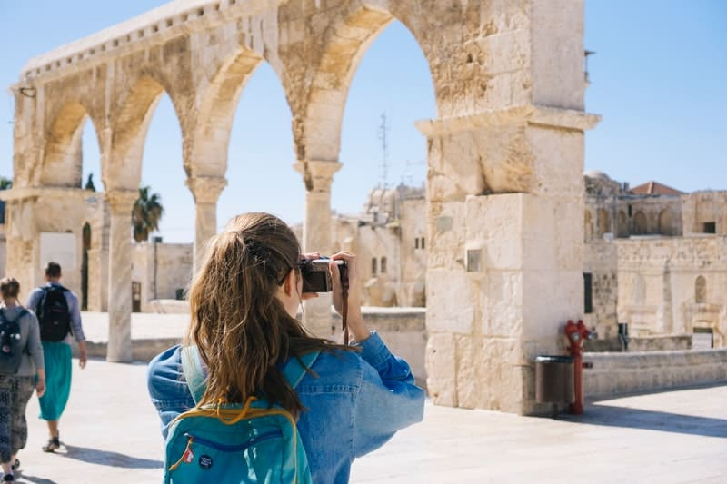 woman taking pictures of ruins wearing blue top and carrying blue pack