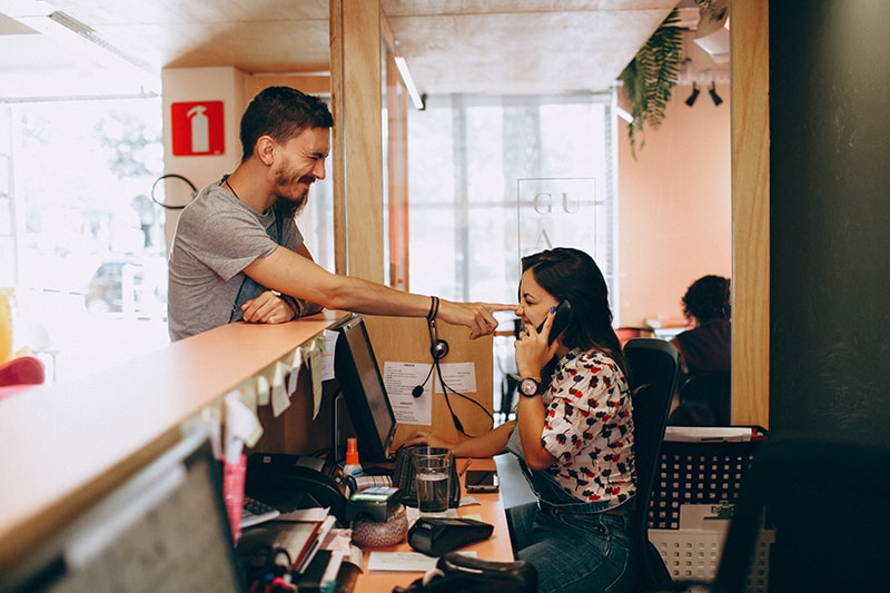 woman talking on phone while the man pokes her nose