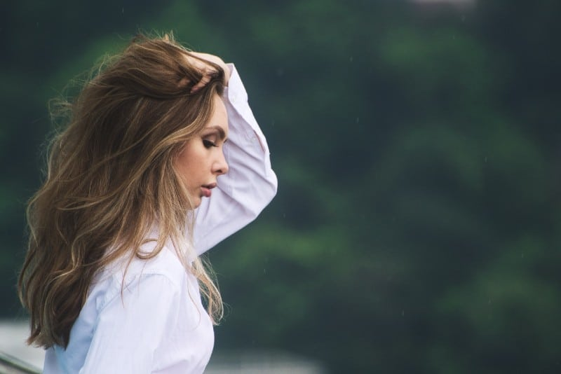 woman in white shirt touching hair