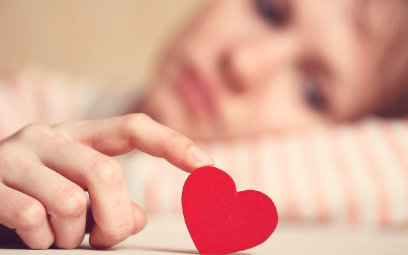 Sad woman touching heart symbol with finger