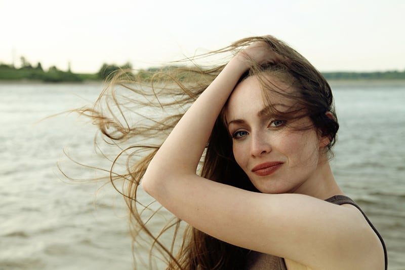 woman touching her hair while standing near the body of water