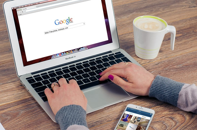 woman using laptop computer and typing on google search