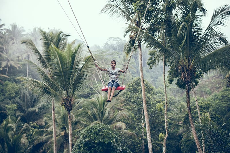 woman using swing surronuded with jungle