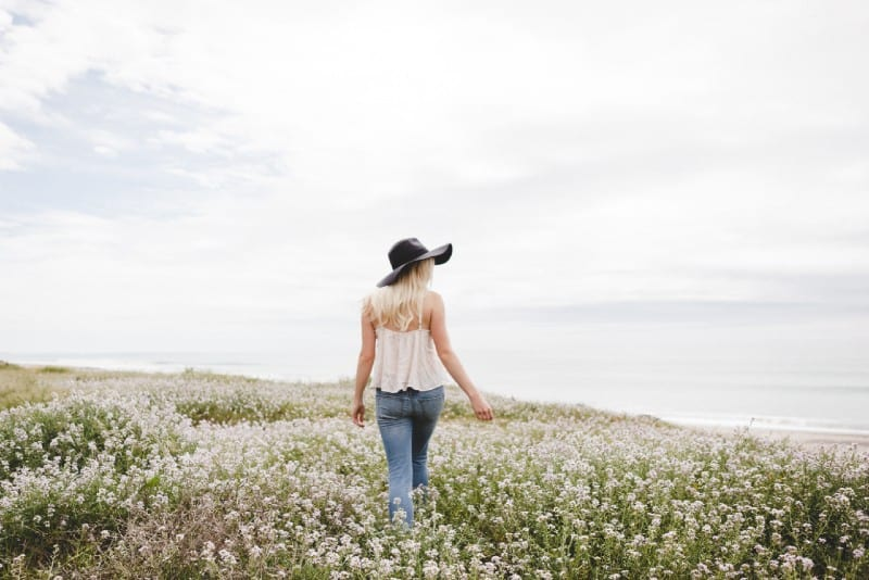 woman wearing black hat walking across the flower field