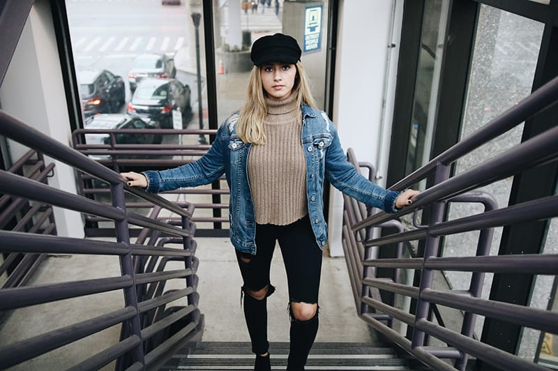 woman wearing blue denim jacket standing in the stairs