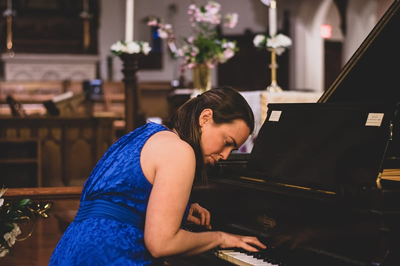 woman wearing blue floral dress playing piano