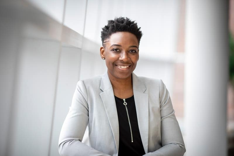 woman wearing gray notch lapel suit jacket with black shirt inside smiling