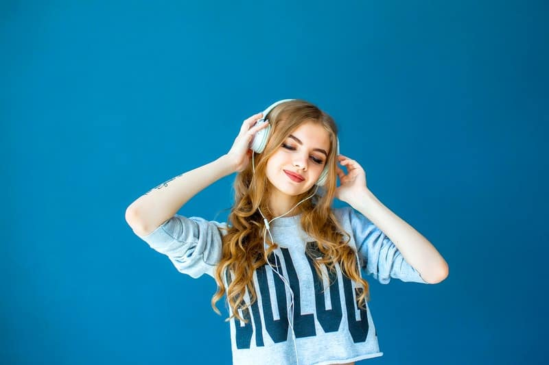woman wearing a headphone in front of a blue wall
