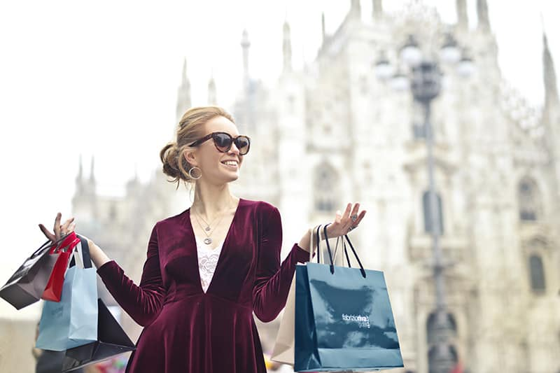 woman wearing maroon velvet long sleeved dress with shopping bags in her hands