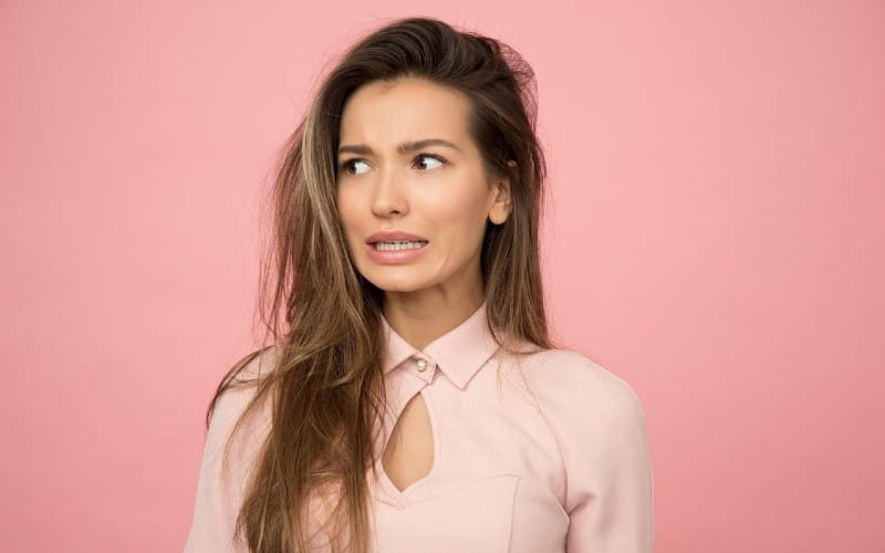 woman wearing pink top standing against pink wall