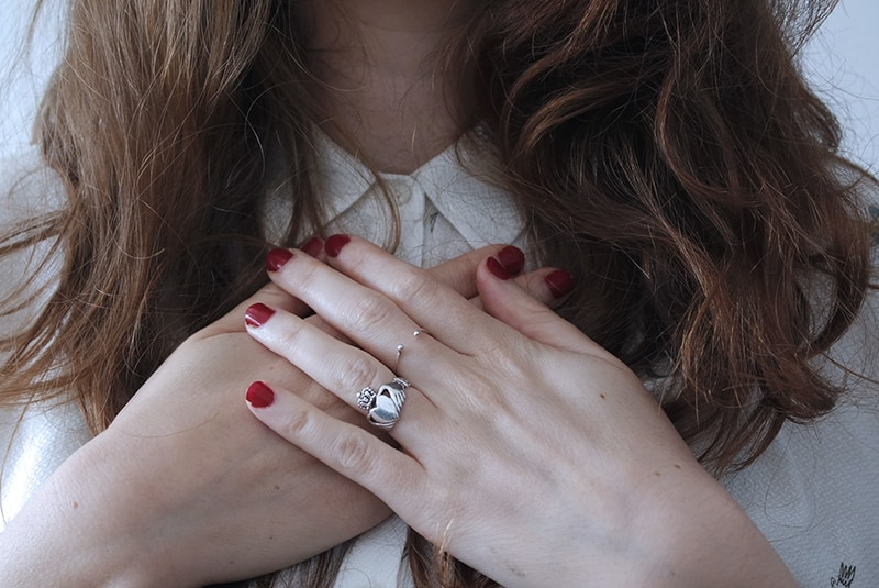 woman wearing silver-colored ring touching her chests