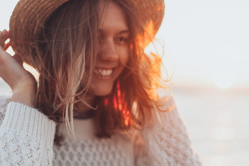 woman wearing white sweater with smile on her face