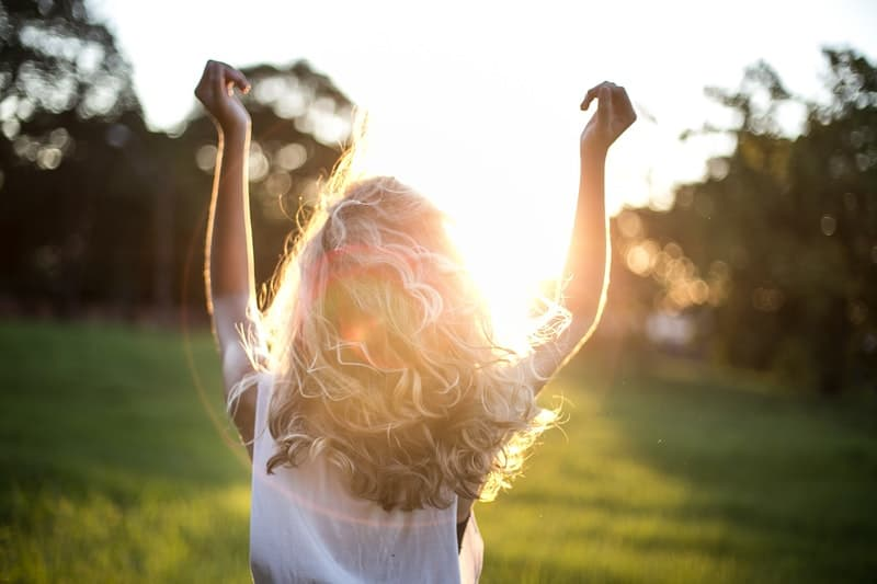 woman wearing white top with hands in the air facing the sun