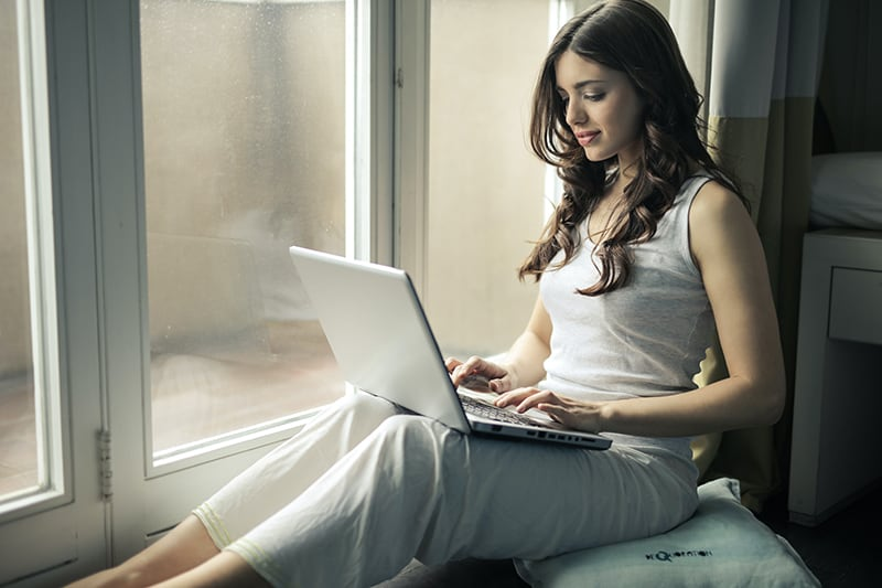 woman wearing white top sitting by the window while using laptop