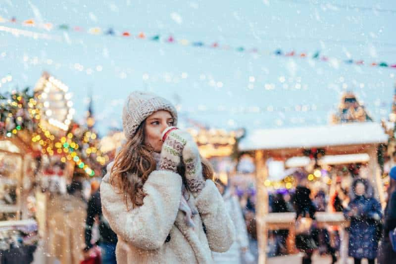 woman wearing winter outfit and drinking coffee at christmas market