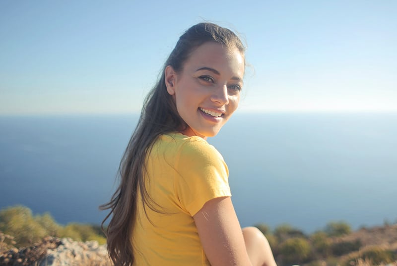 woman wearing yellow shirt sitting on the cliff