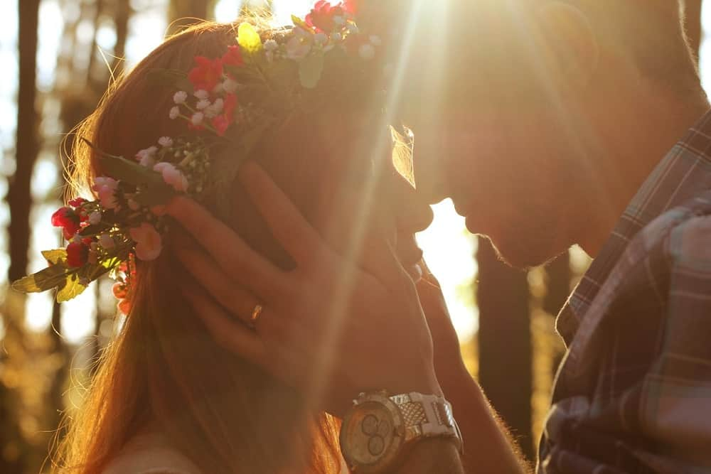 woman wears red and white floral headdress with a man during daytime