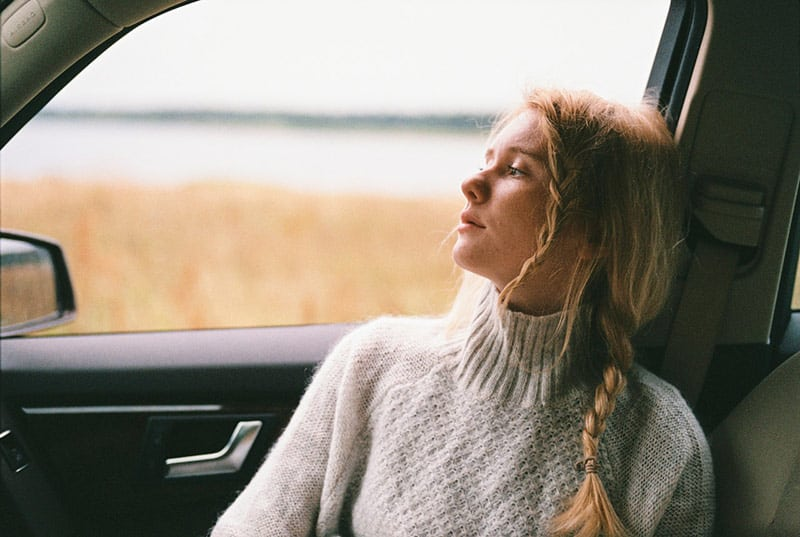 Woman wearing white knit sweater sitting inside car