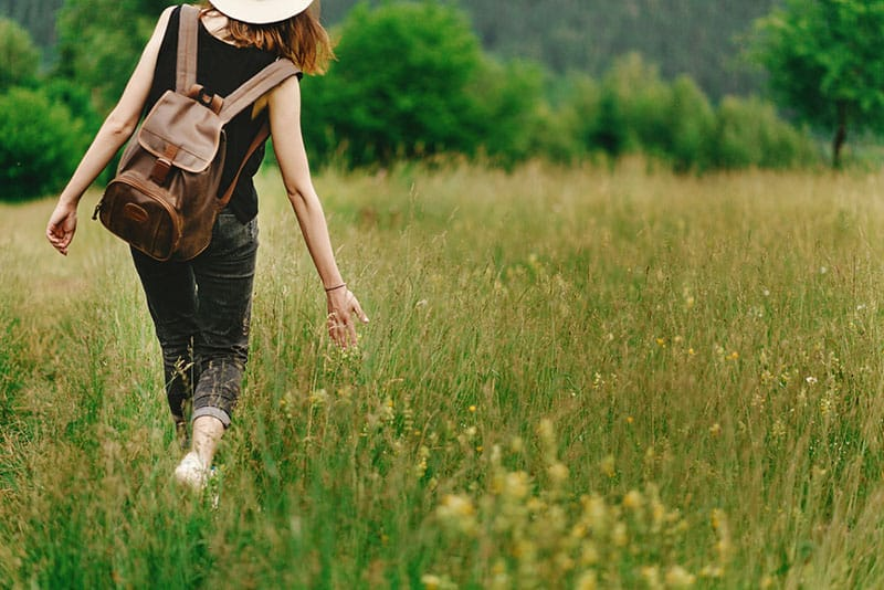 woman with backpack walking through grass