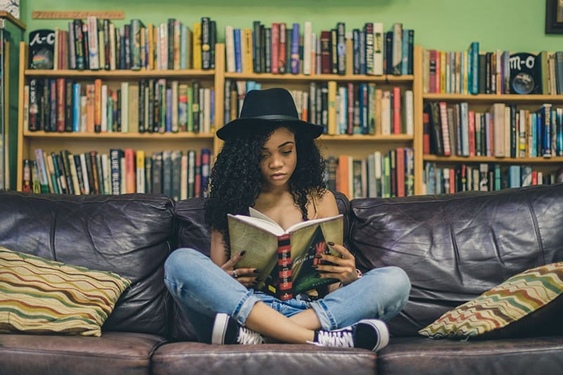woman with black hat reading a book while sitting on black couch