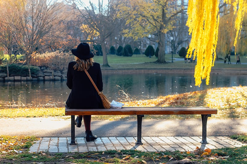 woman with black hat sitting on the bench beside the water