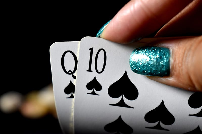 woman with blue nails holding playing cards