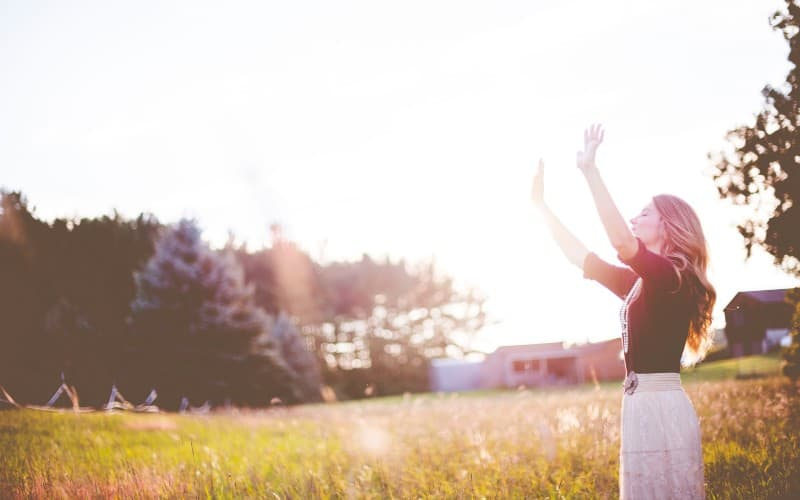 Woman with hands up standing on meadows during daytime