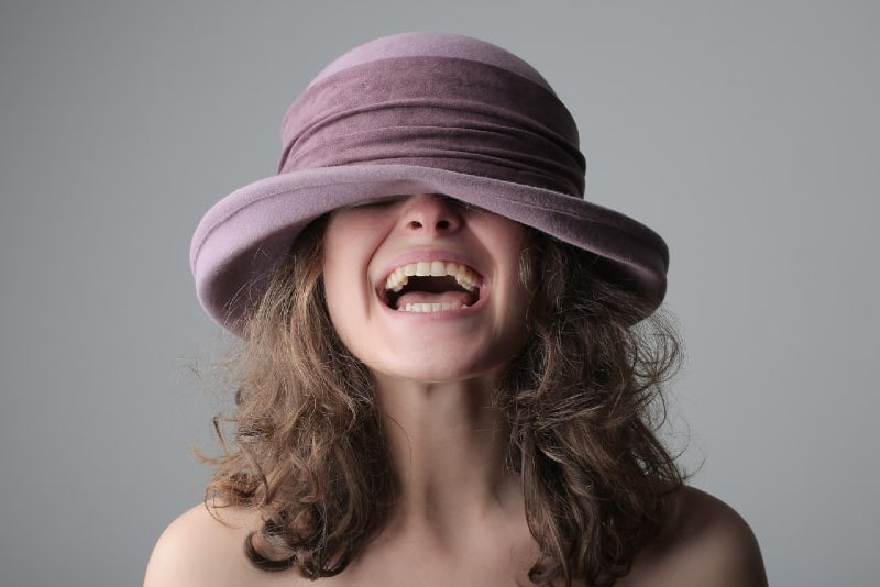 woman in purple hat laughing