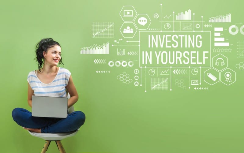 Happy woman sitting on a chair with laptop against green wall and invest in yourself message on it