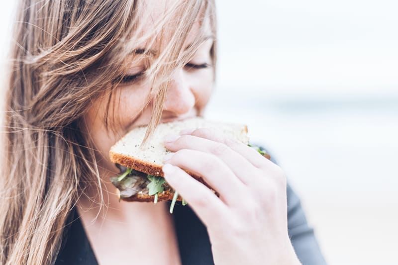 woman with long hair eating sandwich