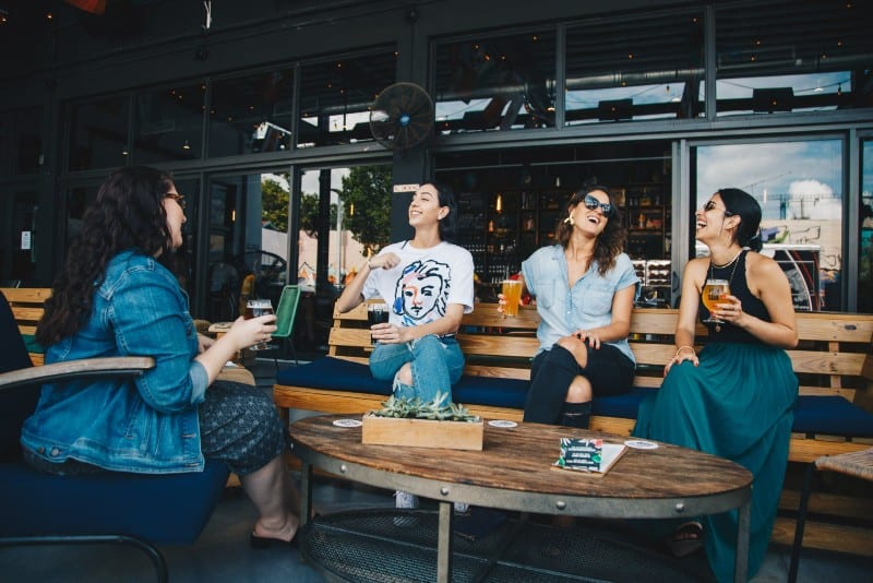 four women drinking beer and chatting outdoor