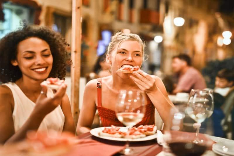 two women eating bruschetta in restaurant