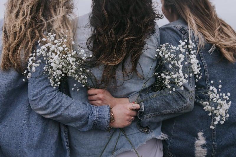 three women facing backward and holding flowers