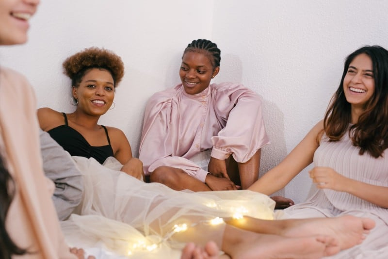 four women sitting on bed and laughing