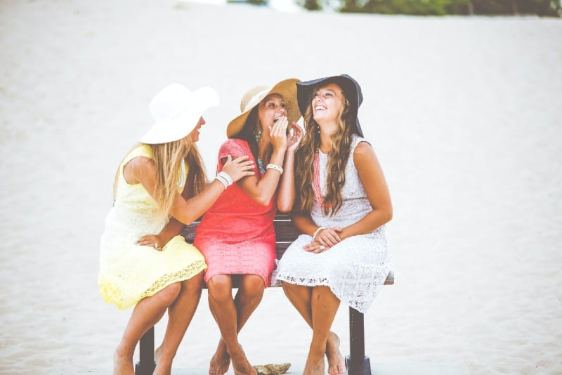 three women with hats laughing while sitting on bench