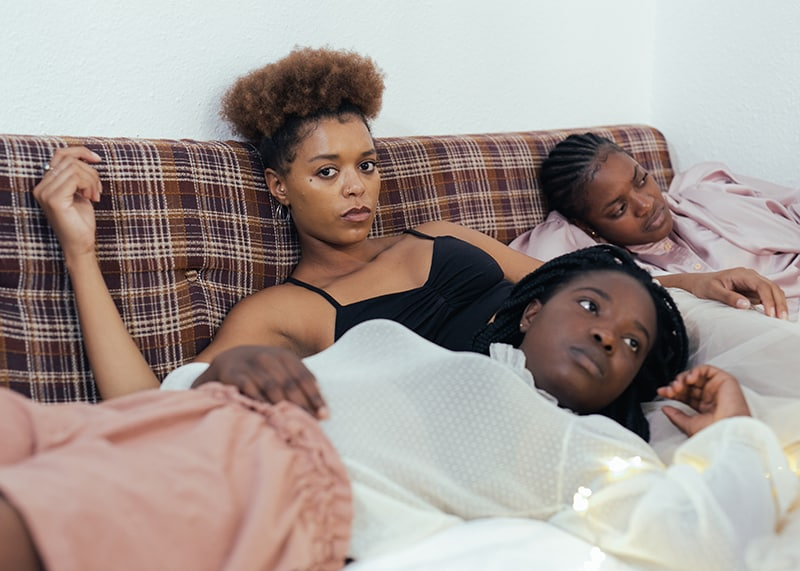 women lying on bed with sad faces