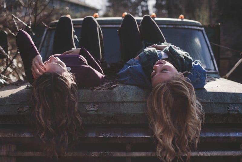 two women lying on old truck