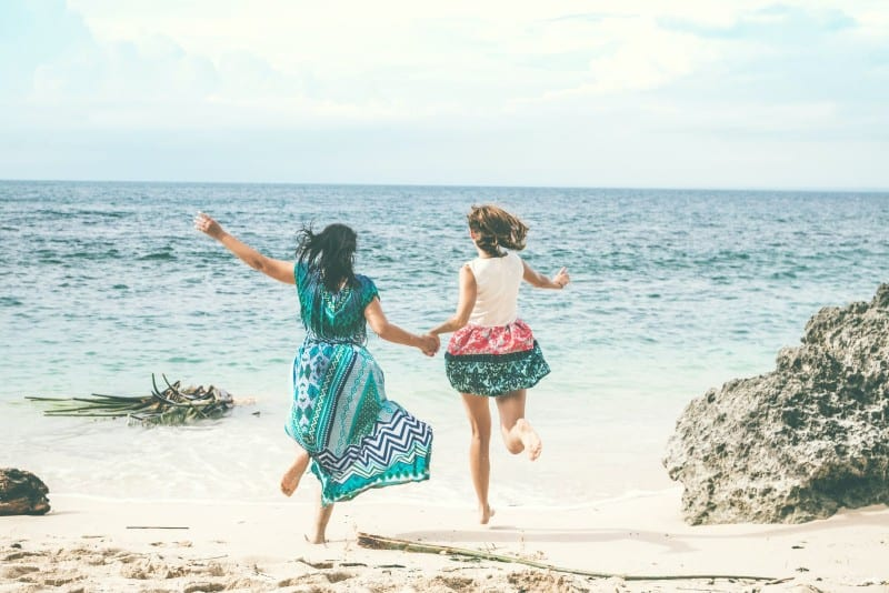 two women holding hands and running at beach