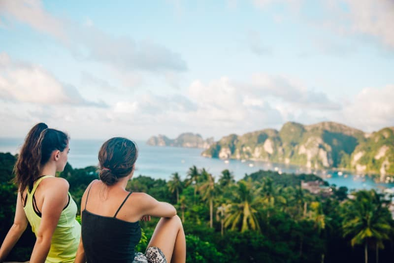 two women sitting on hilltop looking at mountain