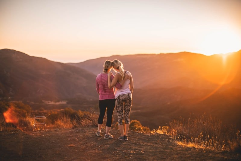 two women standing on mountain at sunset